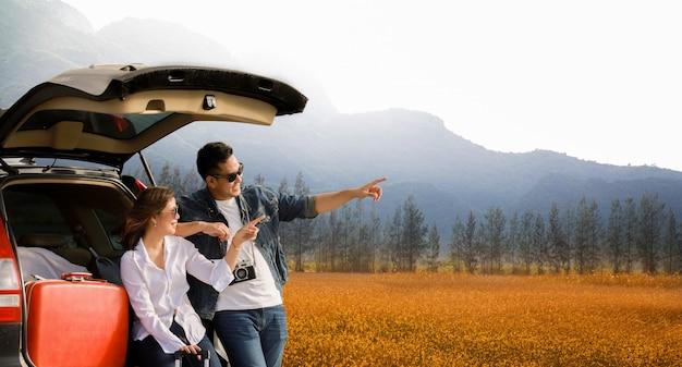 Pareja asiática hombre con camerra vintage y mujer sentada en la parte trasera del coche