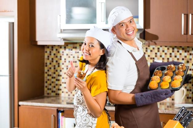 Pareja asiática hornear magdalenas en la cocina de casa