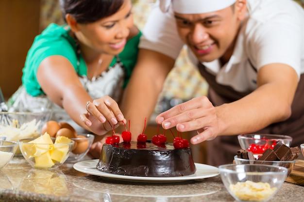 Pareja asiática hornear pastel de chocolate en la cocina