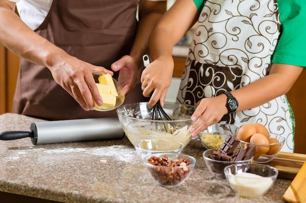 Pareja asiática hornear pasteles en la cocina de casa