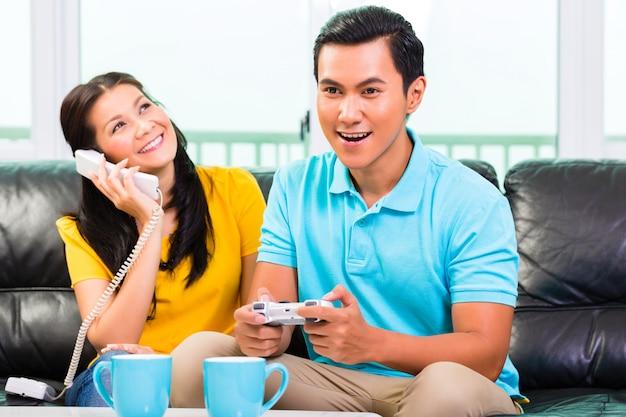 Pareja asiática jugando videojuegos y telefono