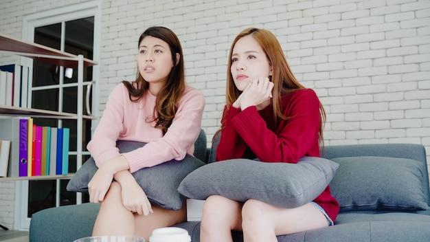 Pareja asiática lesbiana llorando mientras ve un drama en la televisión en la sala de estar en casa