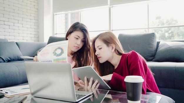 Pareja asiática lesbiana usando una computadora portátil haciendo presupuesto en la sala de estar en casa, dulce pareja disfruta de amor mome