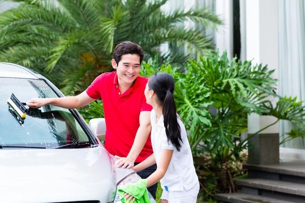 Pareja asiática limpiando juntos coche