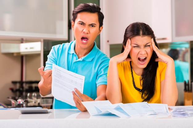 Pareja asiática luchando contra facturas sin pagar