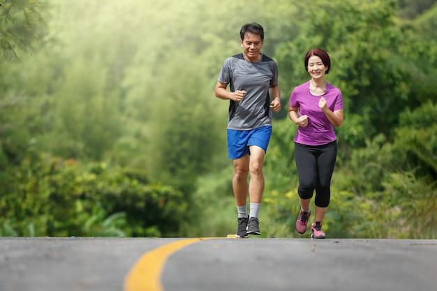 Pareja asiática mediana edad ejercicio para correr en el parque