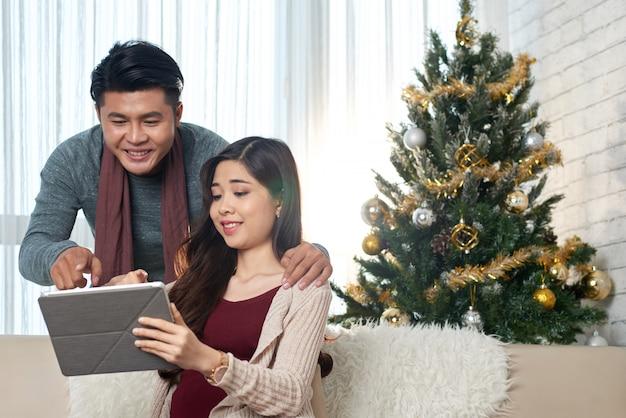 Pareja asiática de mediana edad mirando la pantalla de la tableta juntos en casa en navidad