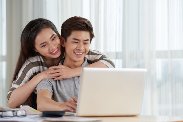 Pareja asiática pasando fin de semana juntos teniendo una videollamada con amigos que viven en el extranjero