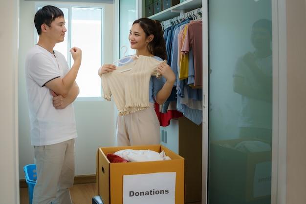 Una pareja asiática está de pie cerca de un armario de ropa en el vestidor y está discutiendo sobre la ropa para donar para llevarla a la caja de donaciones.