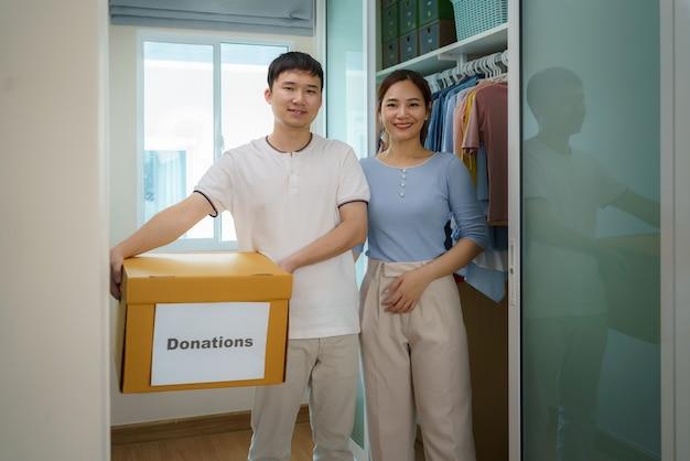 Una pareja asiática está de pie cerca de un armario de ropa en el vestidor llevando una caja de ropa donada para llevar al centro de donación.