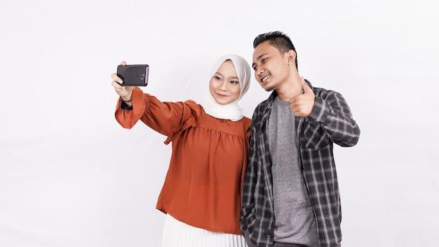 Pareja asiática selfie con espacio en blanco de teléfono