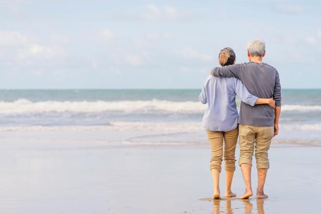 Pareja asiática senior caminando por la playa tomados de la mano. familia de luna de miel juntos felicidad estilo de vida. vida después de la jubilación. plan de seguro de vida