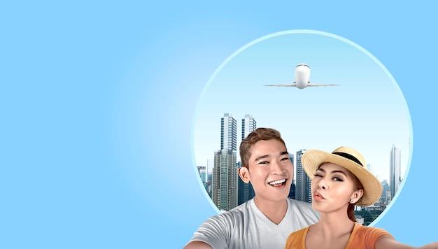 Pareja asiática con sombrero tomando un selfie con fondo de rascacielos