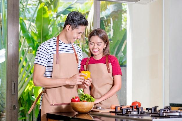 Pareja asiática sonriente cocinando para el almuerzo