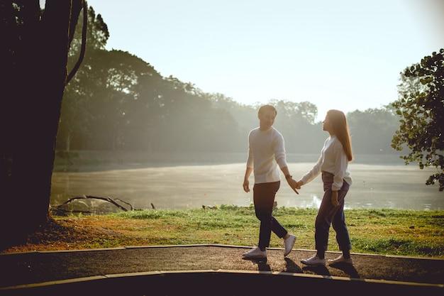 Pareja asiática tiene mano juntos hand. están caminando y hablando alegremente en la mañana con tono sepia.