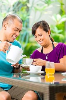 Pareja asiática tomando un café en el porche de casa