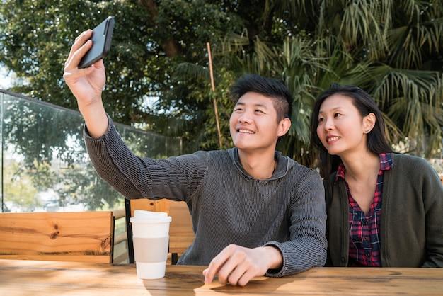 Pareja asiática tomando un selfie con teléfono móvil.