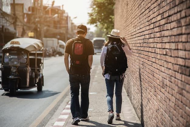 Pareja asiática turista cruzando la carretera