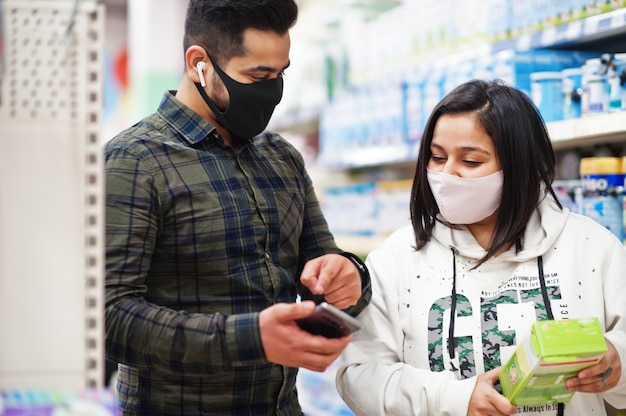 Pareja asiática usa mascarilla protectora comprando juntos en el supermercado durante la pandemia. la compra en línea en un teléfono inteligente es una mejor opción.