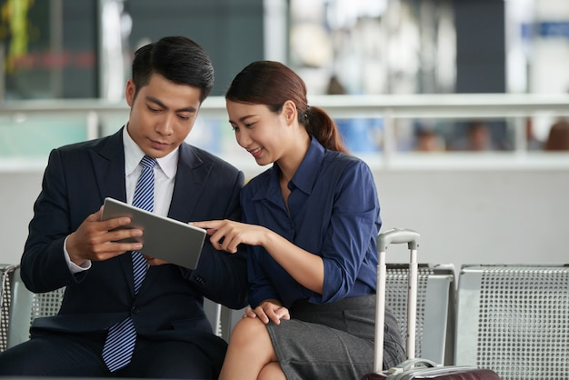 Pareja asiática usando tableta en el aeropuerto