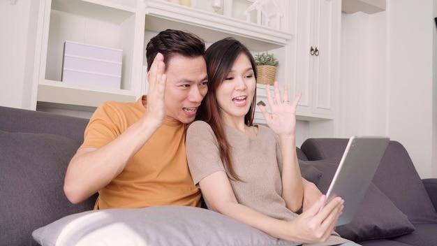Pareja asiática usando tableta video llama con un amigo en la sala de estar en casa