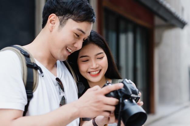 Pareja asiática de viajeros que usa una cámara para tomar una foto mientras pasa un viaje de vacaciones a pekín, china