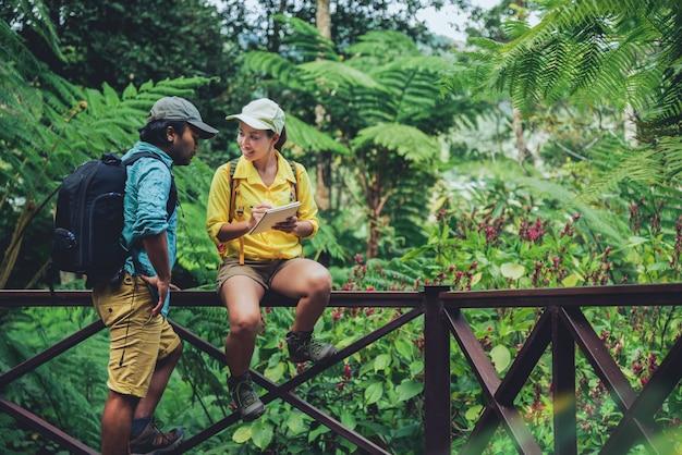 Pareja asiática viajes naturaleza caminando relajarse y estudiar la naturaleza en las fores.