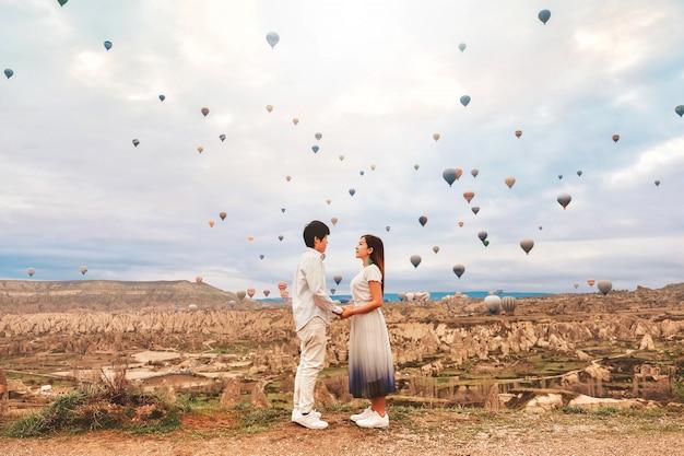 Pareja asiática viendo coloridos globos aerostáticos volando sobre el valle en capadocia, turquía