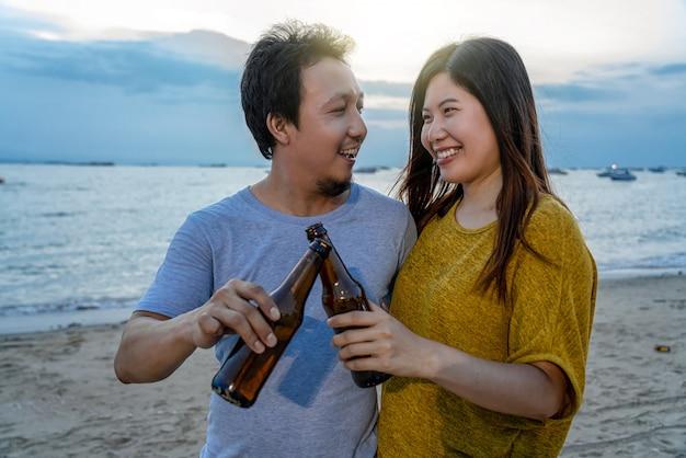 Pareja de asiáticos tiene bebidas de fiesta con botellas de cerveza en la playa