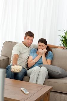 Pareja aterrorizada viendo una película de terror en la sala de estar