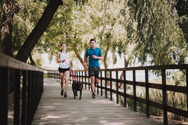 Pareja de atletas corre en green park