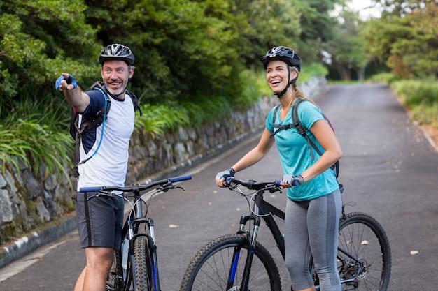 Pareja atlética con bicicleta de montaña apuntando en la distancia