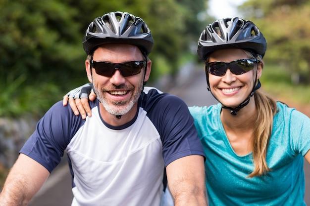 Pareja atlética con cascos mientras monta en bicicleta