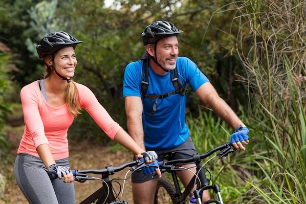 Pareja atlética ciclismo en bosque