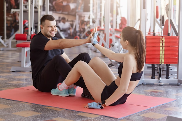 Pareja atractiva joven haciendo ejercicios abdominales mientras está sentado en la estera de yoga en el piso en el gimnasio y dando cinco el uno al otro, mirando sonriente, haciendo ejercicios físicos juntos.