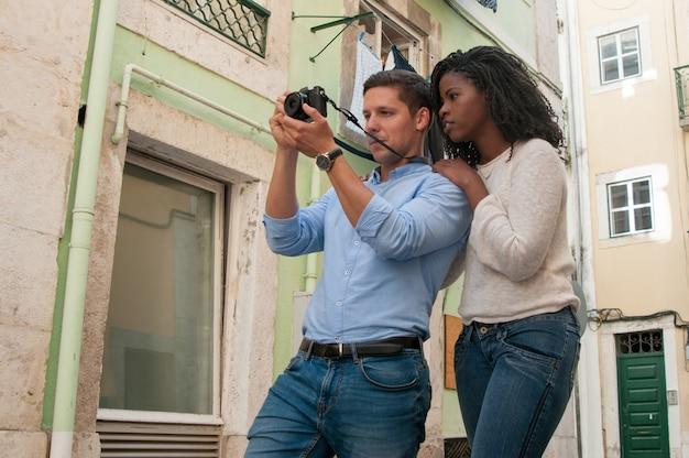 Pareja atractiva positiva tomando fotos en la cámara en la calle