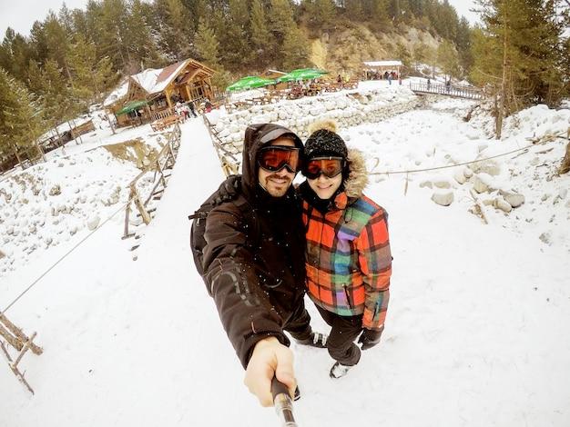 Pareja atractiva tomando selfie impresionante con una cabaña de madera cubierta de nieve