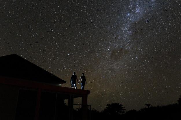 Pareja en la azotea mirando mliky way y estrellas en el cielo nocturno en la isla de bali