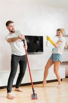Pareja bailando en el interior con objetos de limpieza