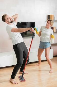 Pareja bailando en el interior con productos de limpieza