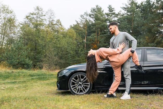 Pareja bailando en la naturaleza cerca de su coche.