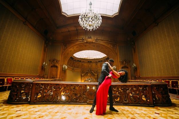 Pareja bailando en una sala antigua