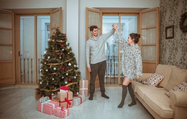Pareja bailando en la sala decorada para navidad