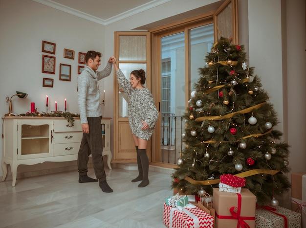 Pareja bailando y tomados de la mano cerca del árbol de navidad