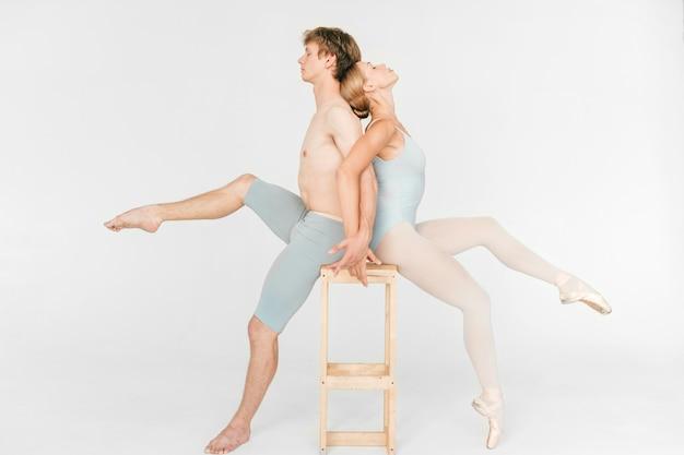 Pareja de bailarines de ballet jóvenes y atléticos sentados en una silla espalda con espalda