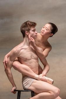 Pareja de bailarines de ballet posando sobre gris.