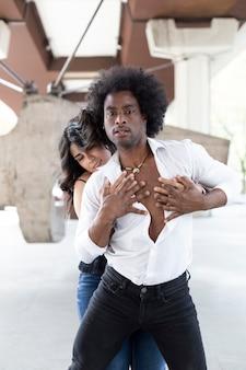 Pareja de bailarines multiétnicos abrazándose apasionadamente los cuerpos en la calle.