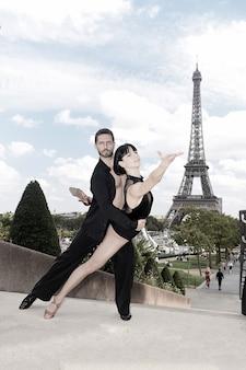 Pareja de baile frente a la torre eifel en parís, francia. hermosa pareja de baile de salón en pose de baile cerca de la torre eifel. concepto de viaje romántico. sentimiento sensual y amor