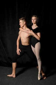 Pareja de ballet posando en medias y leotardo