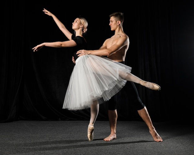 Pareja de ballet posando en tutú y medias
